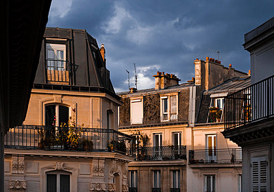 High section of old houses with French balconies against the stormy clouds - p1025m788929f by Peter Karlsson