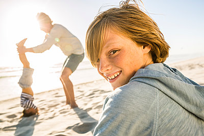 Portrait of smiling boy with father helping son doing a headstand on the beach in background - p300m2167530 by Floco Images