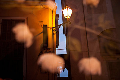 Lights reflected in a window in a street in Italy - p3313576 by Andrea Alborno