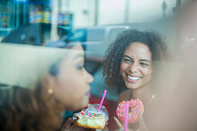 Girlfriends having doughnuts in cafe - p924m2037132 by Seb Oliver