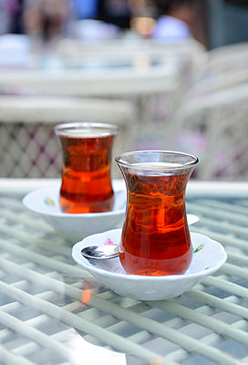 Turkish tea in glass on table - p300m798333f by Hans Lippert
