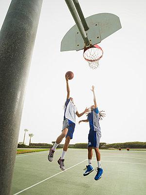 Teenage boys playing basketball on court - p555m1415518 by Erik Isakson