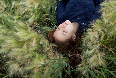 Pensive Caucasian girl laying in field - p555m1521420 by Vyacheslav Chistyakov