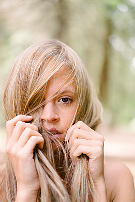 Woman playing with her blond hair - p586m1055875 by Kniel Synnatzschke