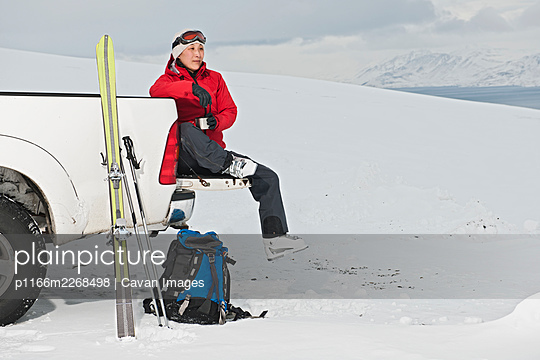 woman sitting on the back of pick up truck taking a break from skiing - p1166m2268498 by Cavan Images