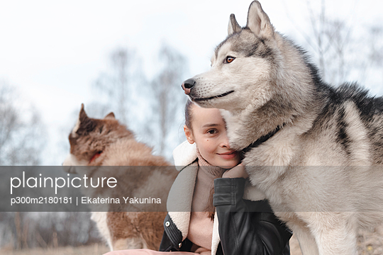 Portrait of smiling woman with her huskies - p300m2180181 by Ekaterina Yakunina
