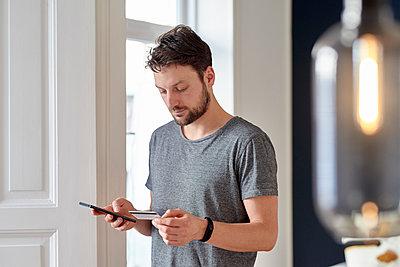 Junger Mann mit Kreditkarte und Smartphone - p1124m1589423 von Willing-Holtz