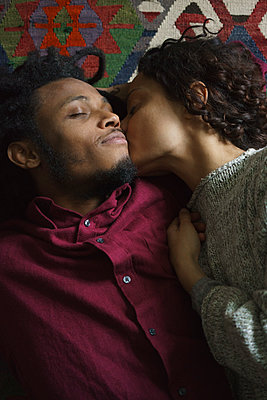 Directly above shot of woman kissing man while lying on carpet - p301m1406338 by Halfdark