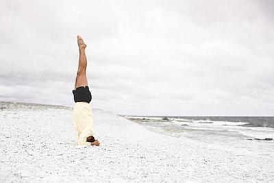 Man doing handstand on sandy beach - p312m2217223 by Michael Jönsson