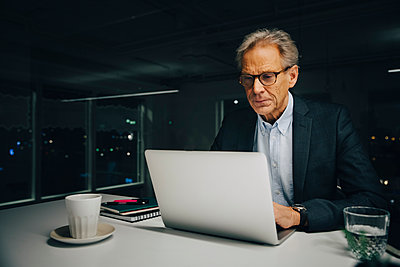 Confident senior businessman using laptop while sitting at illuminated desk in creative office - p426m2194719 by Maskot