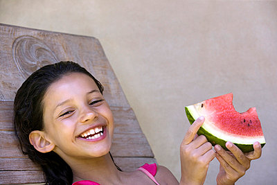 Smiling girl eating watermelon - p42912317f by Easy Production