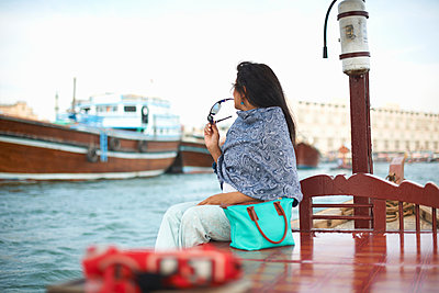 Female tourist sitting on waterfront watching boats on creek, Dubai, United Arab Emirates - p429m1408098 by Peter Muller