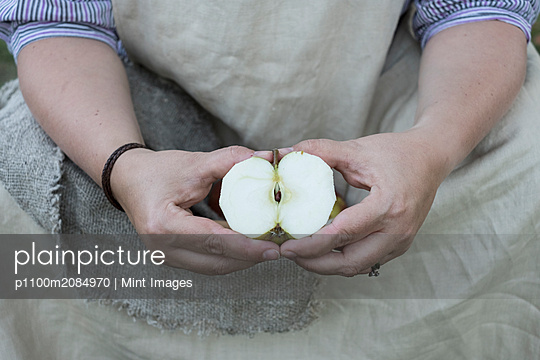 Close up of person holding apple cut in half. - p1100m2084970 by Mint Images