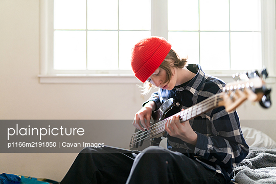 High school student working at home on learning guitar for homework - p1166m2191850 by Cavan Images