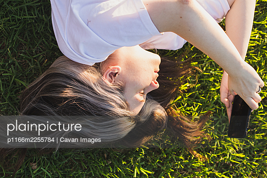 Portrait of girl lying on grass with a phone in her hands at sunset - p1166m2255784 by Cavan Images