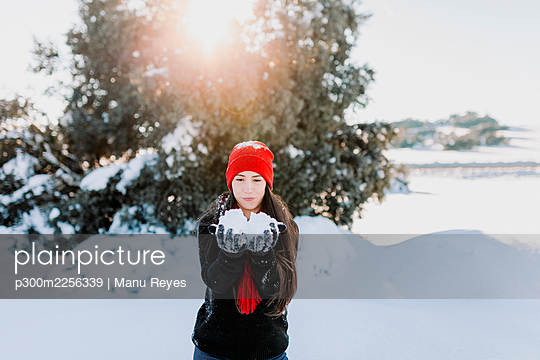Mid adult woman holding snow while standing on land at countryside - p300m2256339 by Manu Reyes