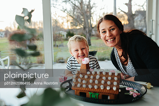 Mother with son making gingerbread house - p312m2086495 by Anna Roström