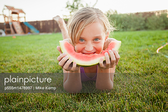 Caucasian girl eating watermelon - p555m1478997 by Mike Kemp