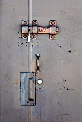 Close-up of closed padlock on metallic door - p1094m1467640 by Patrick Strattner