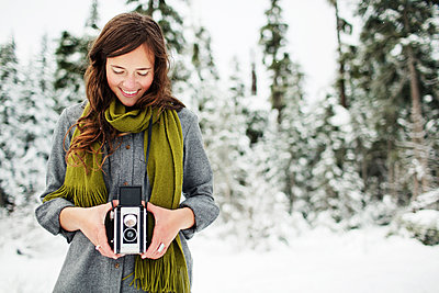 Smiling woman holding camera while standing against snow covered pine trees in forest - p1166m2025256 by Cavan Images