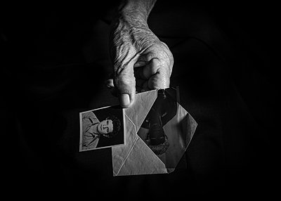 Wrinkled hand holding envelope and vintage passport photograph - p1508m2168809 by Mona Alikhah
