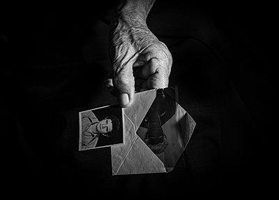 Faltige Hand hält Briefumschlag und ein altes Passfoto - p1508m2168809 von Mona Alikhah