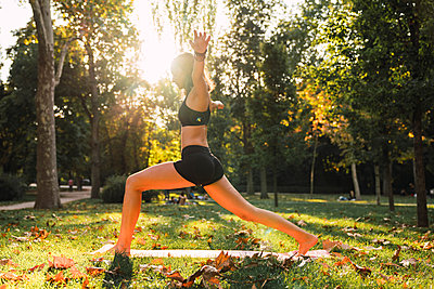 Fit young woman practicing yoga in a park - p300m2059072 von Kike Arnaiz