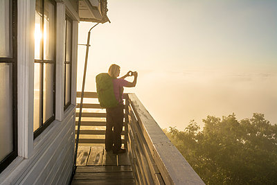 A Woman Enjoy Taking Picture During A Foggy Morning At The Green Knob Firetower - p343m1223857 by Kennan Harvey