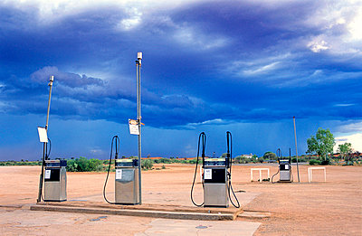 Northern Territory, petrol pumps and approaching thunderstorm in the Outback at Curtin Springs roadhouse - p8552684 by Marcel Malherbe