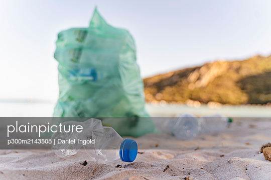 Empty plastic bottles and garbage bin full of collected plastic bottles on the beach - p300m2143508 by Daniel Ingold