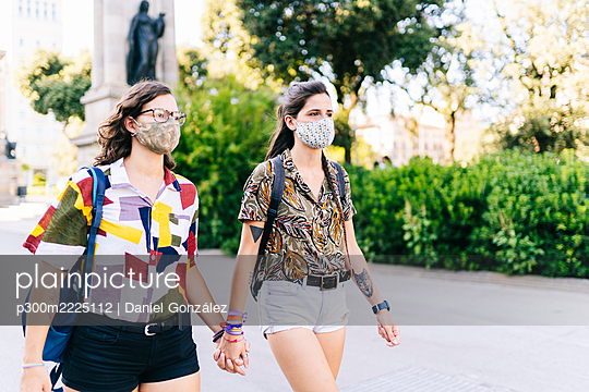 Lesbian couple wearing protective face mask walking on street in city - p300m2225112 by Daniel González
