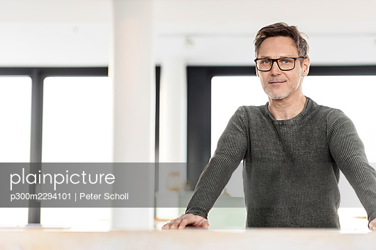 Mature male professional wearing eyeglasses standing at desk in office - p300m2294101 by Peter Scholl