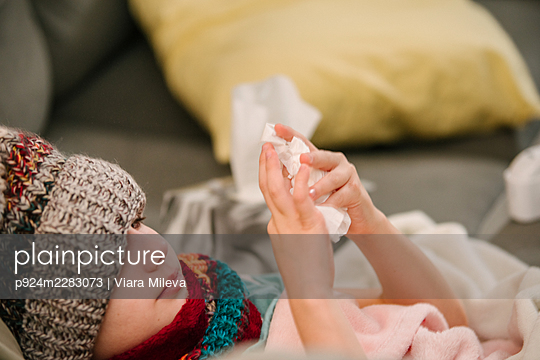 Canada, Ontario, Boy in knit hat holding handkerchief on sofa - p924m2283073 by Viara Mileva