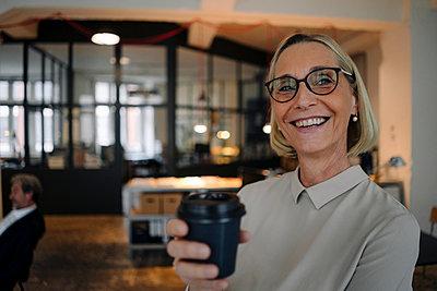 Portrait of happy mature businesswoman having a coffee break in office - p300m2156083 by Gustafsson