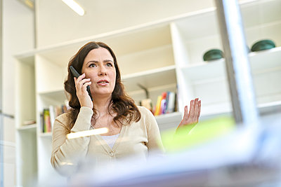 Serious businesswoman talking on mobile phone at workplace - p300m2189437 by Markus Mielek