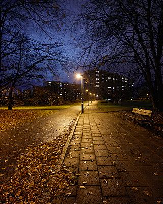 Sweden, Skane, Malmo, Rosengard, Illuminated alley in park at night - p352m1142142 by Gustaf Emanuelsson