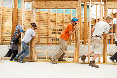 Volunteers pushing framed wall at construction site - p555m1522816 by Roberto Westbrook
