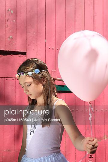 Trauriges Mädchen hält rosa Luftballon - p045m1169549 von Jasmin Sander