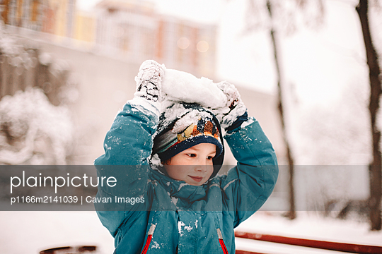 Happy boy playing with snow during winter - p1166m2141039 by Cavan Images