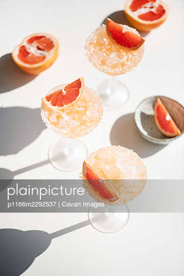 Pink grapefruit margarita cocktails on white background with shadows - p1166m2292537 by Cavan Images