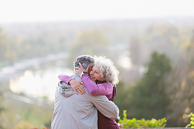 Affectionate active senior couple hugging in nature - p1023m1583900 by Tom Merton