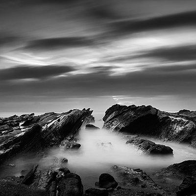 Rocks in sea against dramatic sky - p1166m2060535 by Cavan Social