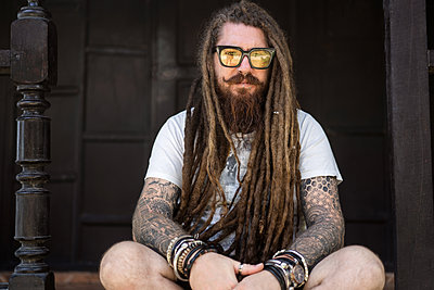hipster guy with dreadlocks and tattoo sitting on the beach in thailan - p1166m2269086 by Cavan Images