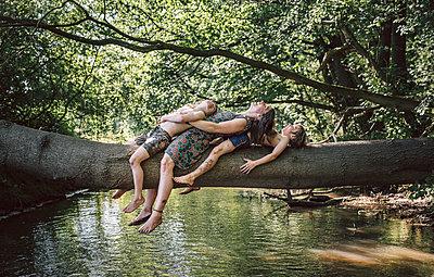 Mutter liegt mit ihren Söhnen auf einem Baumstamm - p1602m2175973 von Frisch Fotografie