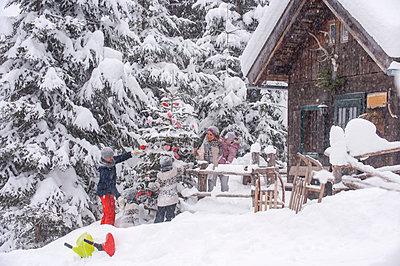 Austria, Altenmarkt-Zauchensee, family decorating Christmas tree at wooden house - p300m2042015 by Hans Huber