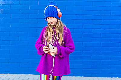 Girl wearing blue cap and oversized pink pullover listening music with headphones in front of blue wall - p300m2102761 von Eloisa Ramos