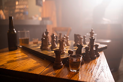 Old wooden chess board and drink on table in a pub - p300m2166169 von VITTA GALLERY