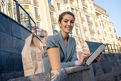 Smiling business holding digital tablet while leaning on railing in city during autumn - p300m2241807 by Vasily Pindyurin