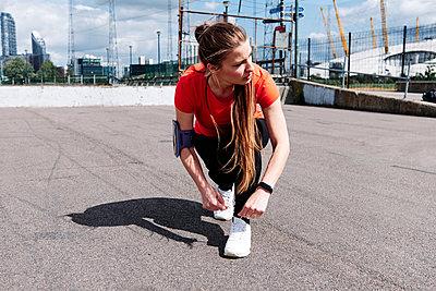 Sportswoman tying shoelace on promenade during sunny day - p300m2287158 by Angel Santana Garcia