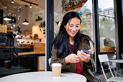 Smiling beautiful woman using mobile phone at sidewalk cafe - p300m2287166 by Angel Santana Garcia